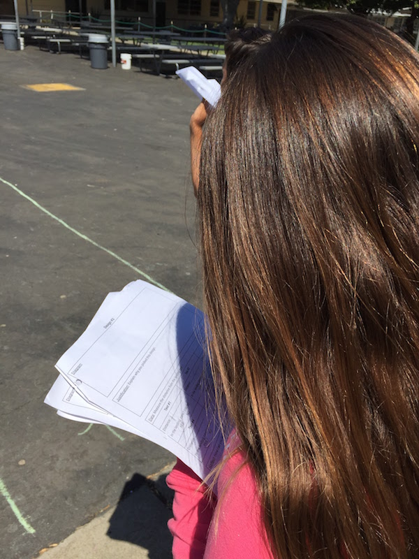 Students tested their paper airplanes in pairs. While one students threw the airplane, the other wrote down the distance and whether or not the airplane landed in the landing zone. Photos c/o Mari Venturino